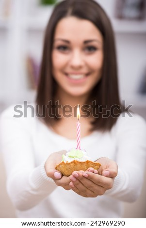 Close-up of birthday cake. Young woman is holding cake with candle. - stock photo
