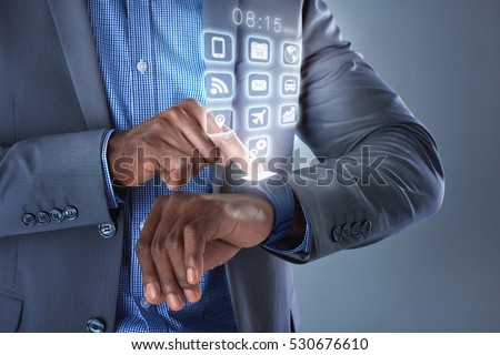 Close up of black african man hands pressing smartwatch displaying hologram apps applications wearable technology futuristic concept