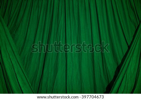 Close up of black draped theatrical curtain or backdrop lit with green gel or filter.