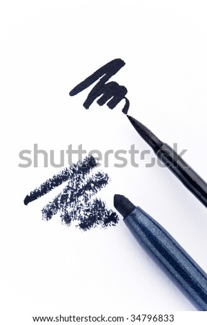 Close up of black eyeliner and pencil on white background - stock photo