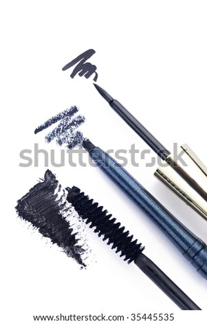 Close up of black eyeliners and mascara brush on white background - stock photo