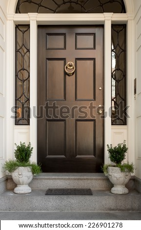 Close Up of Black Front Door with Lunette and Side Windows in White Door Frame with Potted Plants and Doormat - stock photo
