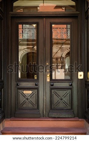 Close-up of Black Front Double Doors with Crosshatch Detail and Windows - stock photo