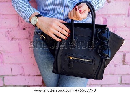 Close up of black leather handbag in hand of stylish woman. Female fashion and accessories.