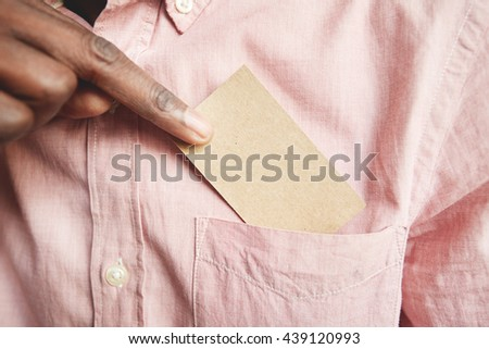 Close up of black male holding blank visiting card. Young African businessman pulling out business card from the pocket of his polo shirt, exchanging information with a potential partner. Film effect