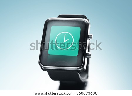 close up of black smart watch with clock icon - stock photo