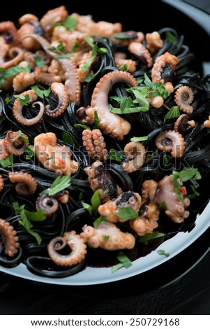 Close-up of black tagliatelle with sliced baby octopuses - stock photo