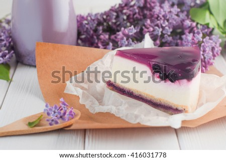 Close up of blackberry cheesecake slice near bilberry milkshake and lilac flowers on the white wooden background. Selective focus and small depth of field. - stock photo