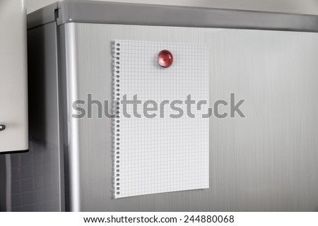 Close-up Of Blank Paper Posted On Modern Refrigerator Door - stock photo