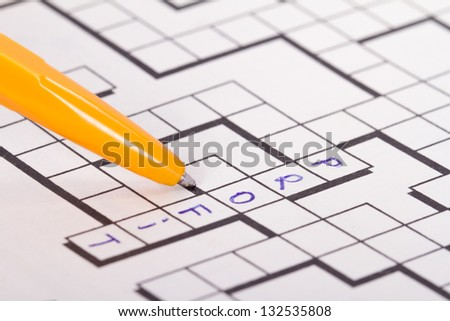 Close up of blank square crossword puzzle with pen and profit text. - stock photo
