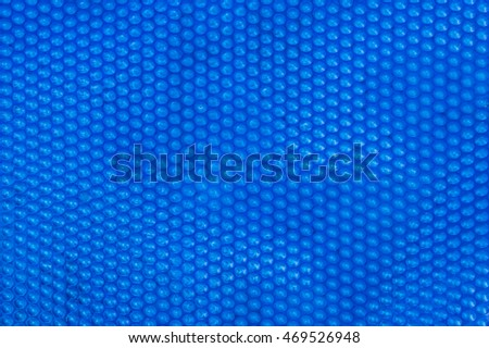 Close up of blue bubble plastic used as a swimming pool insulation cover to prevent evaporation of water and to retain the heat