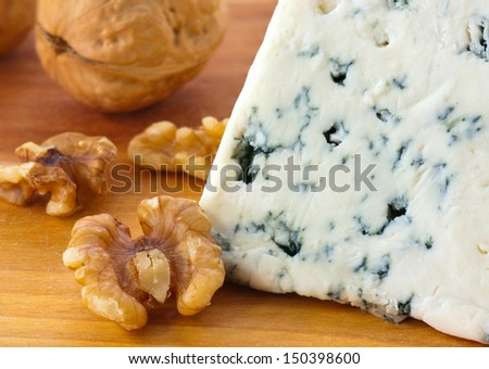 Close-up of blue cheese and walnuts on wood cheese board. Shallow DOF. - stock photo