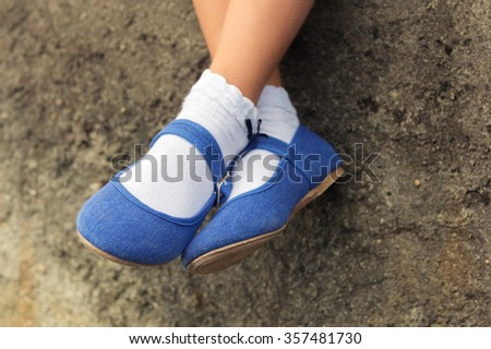 Close up of blue denim ballerinas  on child's feet - stock photo
