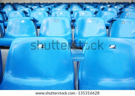 Close up of blue grandstand for fans with numbers at football stadium. - stock photo