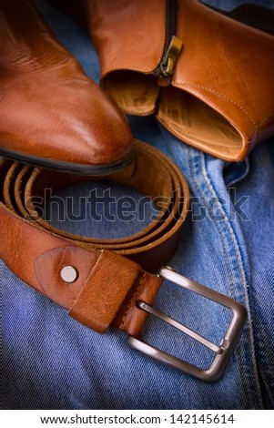 Close-up of blue jeans, boots and belt.