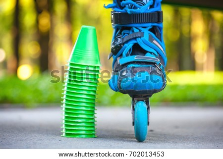 Close up of blue roller skates with cones lying on asphalt.