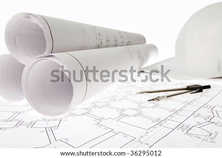 Close-up of blueprints with sketches of projects, helmet and dividers on them - stock photo