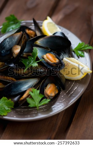 Close-up of boiled mussels with lemon and fresh parsley