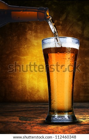 Close up of bottle of beer pure into a glass. Cold refreshment - stock photo