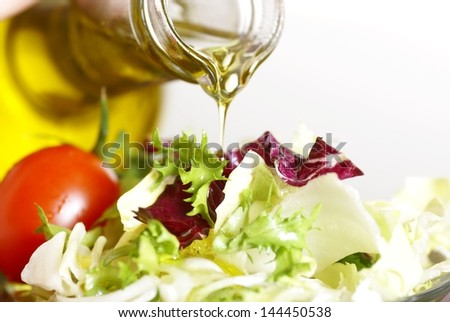 Close-up of bottle with pouring olive oil and vegetable salad - stock photo