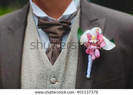 close up of boutonniere on groom brown suit outdoors - stock photo