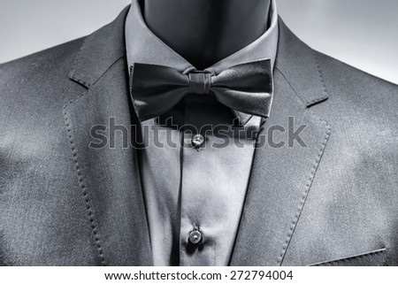 Close up of bow tie over elegant grey suit. Black White