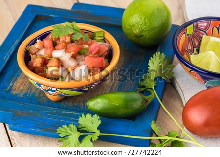 Close up of bowl with chunky salsa pico de galla and ingredients.