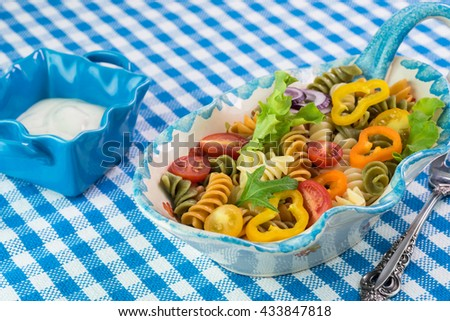 Close up of  bowl with summer veggie pasta on a table.