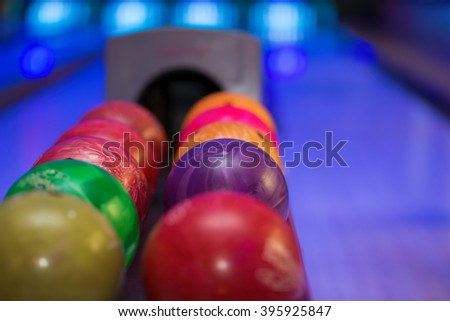 Close up of bowling balls with bowling lane in the background.