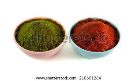 close up of bowls of red and gree  thai curry paste isolated