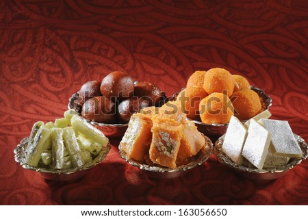 Close-up of bowls of traditional Indian sweets - stock photo