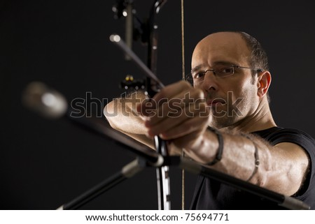 Close up of bowman in black on black background aiming with bow and arrow, side view with focus on eyes.