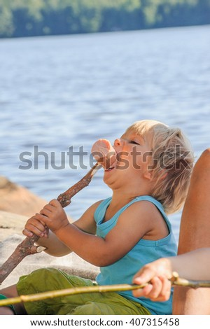 Close up of boy eating a sausage on a grilling stake. There's water in the background - stock photo