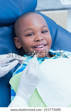 Close up of boy having his teeth examined by a dentist - stock photo