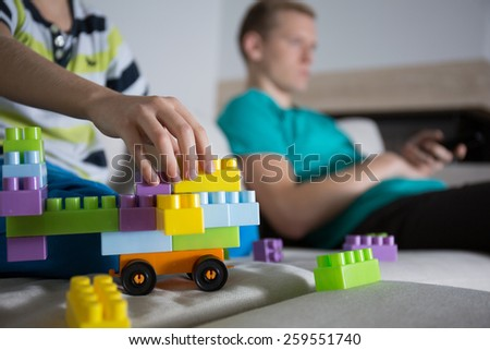 Close-up of boy playing with colorful blocks in family room - stock photo