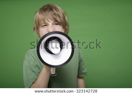 Close up of boy screaming in megaphone against green background