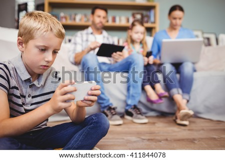 Close-up of boy using mobile phone while family with technologies in background - stock photo