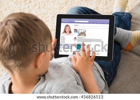 Close-up Of Boy Using Social Networking Site On Digital Tablet At Home
