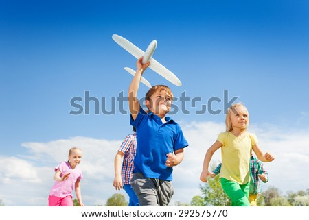 Close-up of boy with airplane toy and children - stock photo