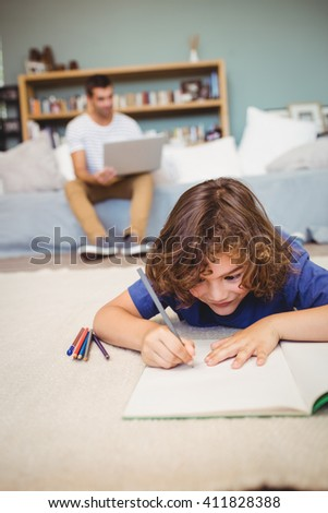 Close-up of boy writing in book while father working in background - stock photo