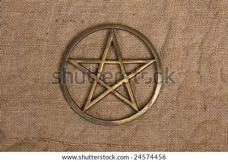 close up of brass pentacle on hessian burlap background