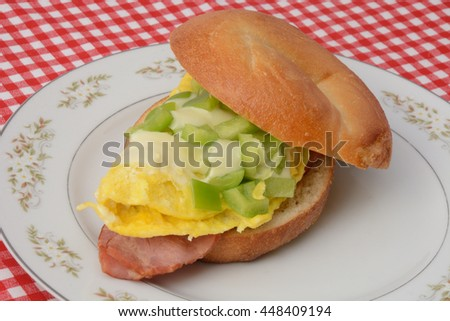 Close up of breakfast cheese omelet with sliced green peppers with turkey bacon on bagel
