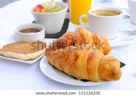 close-up of breakfast with croissants in white plate, coffee orange juice and fresh fruits in background