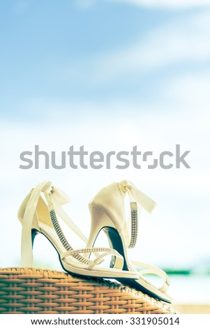Close-up of bridal shoes with crystal necklace. Shallow depth of field. Cross process. - stock photo