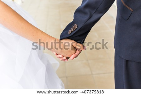 Close-up of Bride and groom holding hands outdoors.