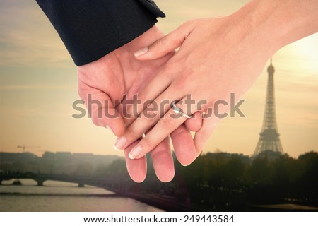 Close-up of bride and groom with hands together against eiffel tower