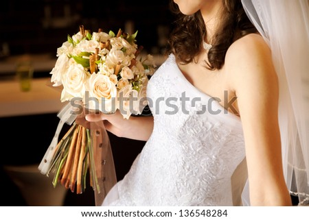Close-up of bride holding  bouquet of pink roses - stock photo