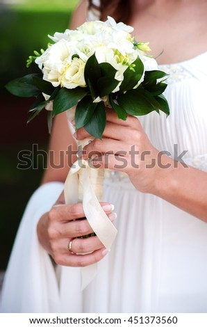 Close-up of bride's hand with a bouquet of roses and lilies.