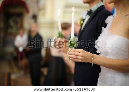 Close-up of bride's hands holding white candle decorated with greenery