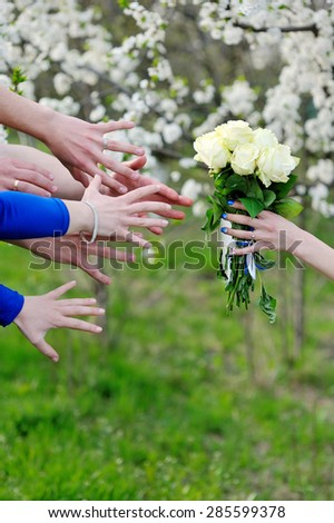 Close-up  of bridesmaids stretching their hands to take wedding bouquet from bride - stock photo